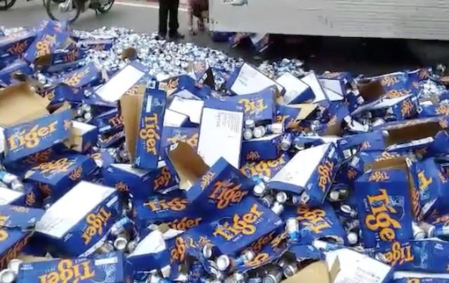 Dân giúp tài xế gom hàng trăm thùng bia đổ ra quốc lộ Ảnh 1