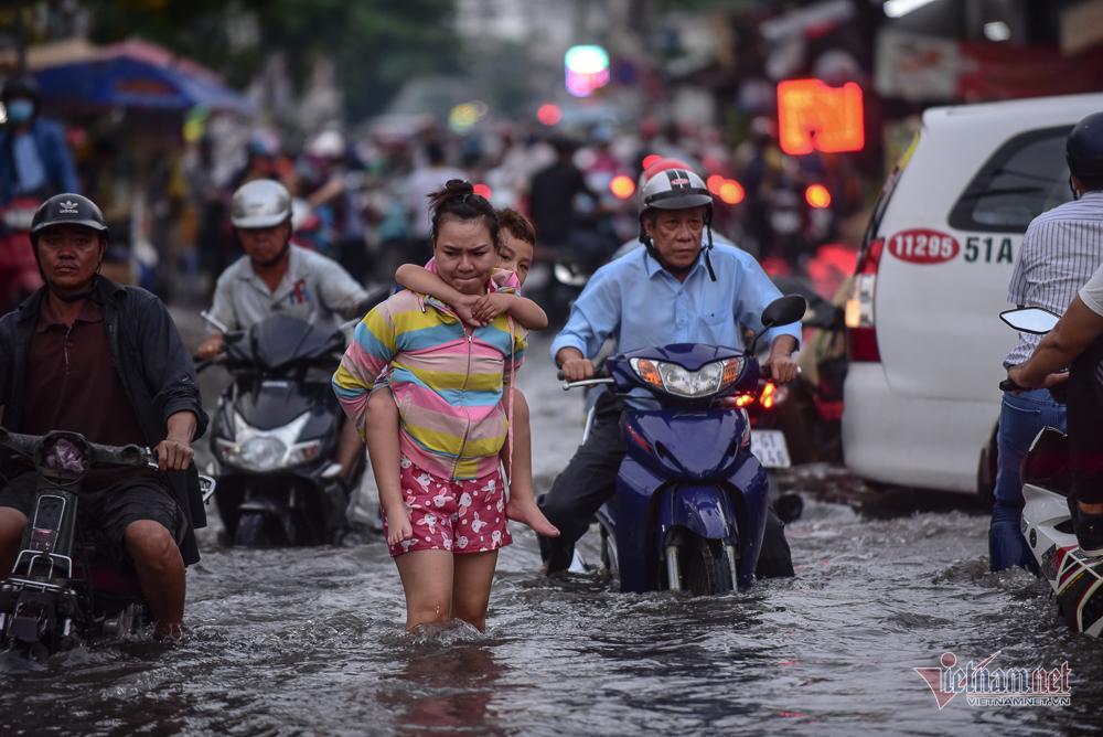 Mẹ bồng con mò mẫm lội đường Sài Gòn ngày triều cường kỷ lục Ảnh 2
