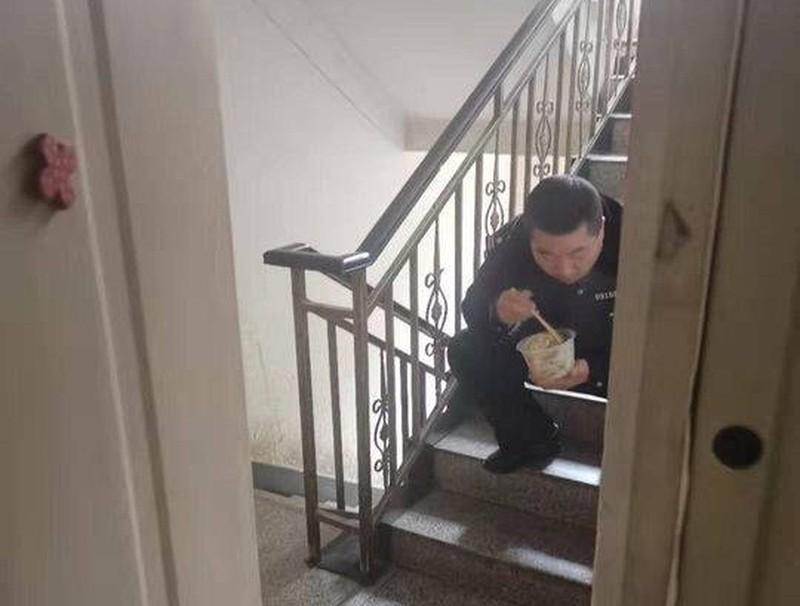 Sợ lây bệnh cho vợ con, cảnh sát ngồi ăn ở cầu thang, nhét bát qua khe cửa khiến bao người xót xa Ảnh 1