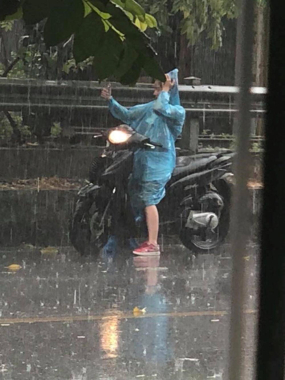 Cô gái dừng xe chụp ảnh dưới cơn mưa rào đầu tiên của Hà Nội sau đợt nắng nóng kéo dài \