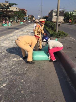 CSGT và người dân thu dọn 10 tấn ngô rơi vãi ra đường