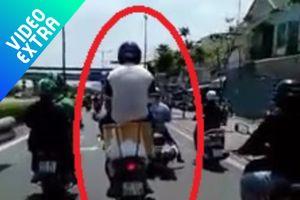 Người đàn ông ngồi trên thùng hàng xe máy một cách nguy hiểm