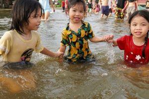 Trẻ em thỏa thích bơi lội trên... đường tỉnh lộ ở Hà Nội