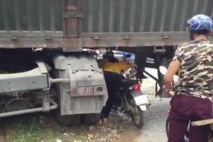 Container chắn ngang quốc lộ, dân dắt xe máy chui qua gầm