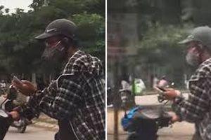 Thanh niên bất chấp nguy hiểm vừa đi xe máy vừa chơi điện tử