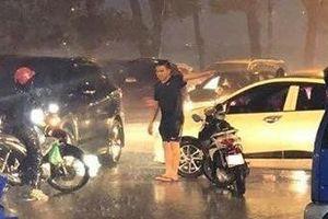 Chàng trai chủ động đứng phân làn đường giữa trời mưa lớn