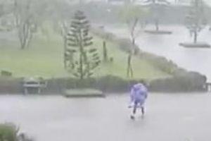Nam sinh cõng bạn gái giữa cơn mưa lớn