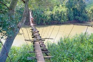 Người dân thấp thỏm vượt qua những cây cầu treo giữa dòng nước cuồn cuộn