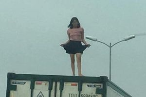 Người phụ nữ mặc váy ngắn nhảy múa trên nóc xe container