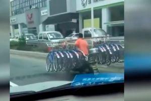 Người đàn ông đi xe máy một tay... gánh 16 chiếc xe đạp