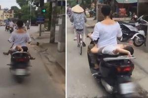 Mẹ chở con nằm ngửa trên yên xe máy khiến người đi đường thót tim