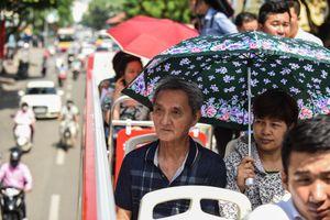 Khách dùng ô che nắng đi xe buýt hai tầng ở Hà Nội