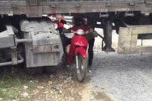 Ôtô đầu kéo mắc kẹt ngang đường, dân chui qua gầm để di chuyển