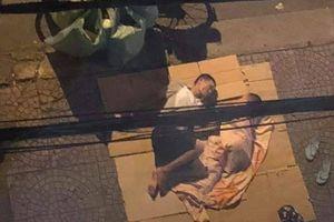 Bức ảnh hai cha con nằm ngủ trên tấm bìa các tông ở vỉa hè, bên cạnh chiếc xe đạp chở phế liệu khiến bao người xúc động