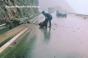 Chàng thanh niên đứng giữa mưa, đẩy đá to ra khỏi đường đèo