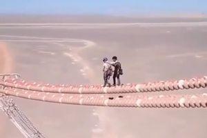 Các công nhân vô tư đi bộ trên dây điện cao hơn chục mét