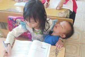 Vừa bế em vừa học bài, tấm hình chụp cô bé tiểu học khiến nhiều người xót xa