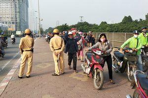 Đoàn người dắt xe máy ngược chiều trên phố Hà Nội để 'né' bị CSGT phạt có phạm luật?
