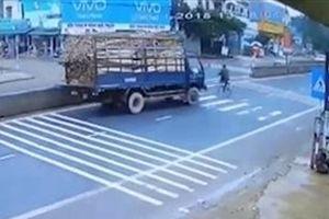 Tránh cụ ông sang đường ẩu, xe tải chở gỗ lật nhào