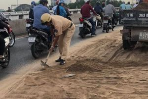 CSGT cùng người dân hì hục dọn cát rơi vãi trên đường