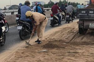 CSGT cặm cụi dọn đất cát trên cầu vượt ở TP.HCM