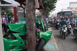 TP.HCM: Sau gây tai nạn liên hoàn, xe taxi 'dính chặt' vào gốc cây