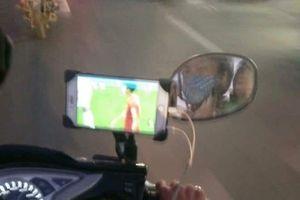 Vừa lái xe vừa dùng điện thoại xem Việt Nam đá, tài xế xe ôm khiến nhiều người lo lắng