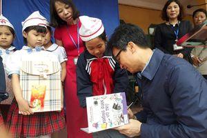 Phó thủ tướng Vũ Đức Đam lì xì sách cho học sinh