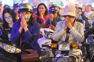 Ngồi xe máy giữa lòng đường chắp tay cầu bình an