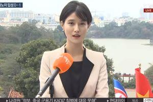 Phóng viên đài Yonhap đưa tin với bối cảnh thủ đô Hà Nội phía sau