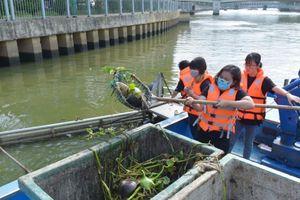 Nữ tình nguyện viên dọn rác trên kênh Nhiêu Lộc - Thị Nghè