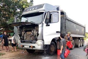 Người dân dùng xô xách nước dập lửa trên xe tải