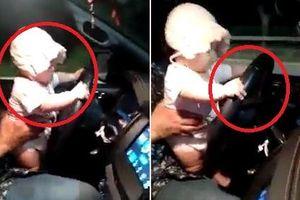 Bố để con vài tháng tuổi lái ô tô, mẹ ngồi cạnh hớn hở quay clip