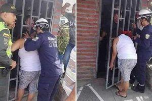 Ngó nghiêng nhà hàng xóm, phụ nữ bị mắc kẹt đầu vào song cửa