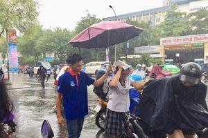 Thanh niên tình nguyện che mưa cho thí sinh dự thi THPT quốc gia