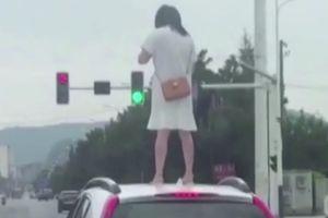 Cãi nhau với chồng, người vợ Trung Quốc leo lên nóc ôtô giữa đường