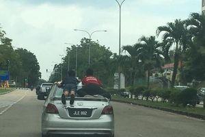 Hai bé trai Malaysia nằm vắt vẻo trên nắp cốp xe ôtô đang chạy