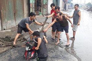 Tình huống éo le: Chiếc xe máy bị đường lớn 'nuốt' đầu trong ngày mưa lớn