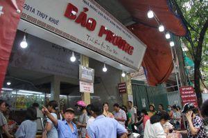 Mưa lớn, cửa hàng phát áo mưa cho khách đang chờ mua bánh trung thu