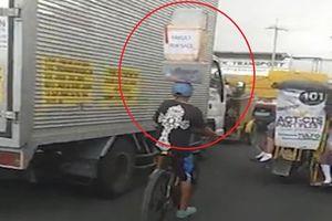 Cậu bé vừa giữ thùng hàng trên đầu vừa đạp xe
