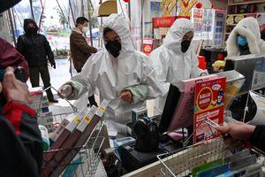 Nhân viên Trung Quốc mặc đồ bảo hộ kín người đứng bán hàng