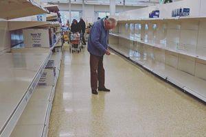 Ảnh cụ ông đứng giữa kệ hàng trống ở siêu thị