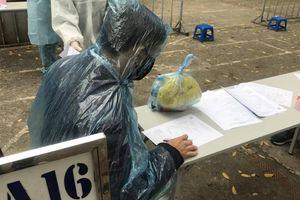 Chùm ảnh: Người dân Hà Nội căng thẳng, mặc cả áo mưa đi test nhanh Covid-19