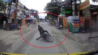 Tài xế xe máy ngã trước đầu ôtô vì mải mê dùng điện thoại