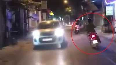 Nữ tài xế lái xe máy lạng lách giữa đường Hà Nội đầy xe cộ