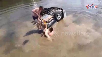 Khoảnh khắc giải cứu gia đình bị mắc kẹt trong xe ô tô lập úp dưới sông
