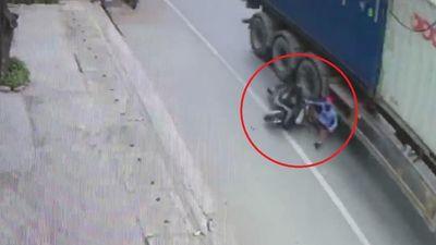 Người phụ nữ đi xe máy thoát chết khi ngã vào container