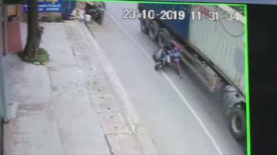 Lạnh gáy chứng kiến cảnh người phụ nữ ngã nhào vào bánh xe container