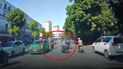 Ngồi trên xe chở đồ cồng kềnh, người đàn ông tuột khỏi xe máy khi chạy trên phố