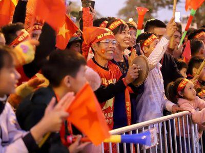 Hàng trăm CĐV từ nhiều tỉnh thành nhuộm đỏ khu vực phía trước sảnh VIP sân bay quốc tế Nội Bài. Họ nhảy múa, ca hát chờ nhà vô địch bóng đá Đông Nam Á.